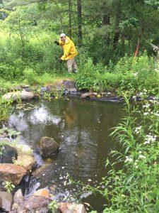 Adam Kohl gardening near a pond